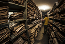 Caucasian man searching old newspapers in library archive