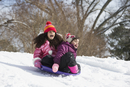 Hispanic children sledding in snow