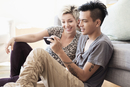 Couple using cell phone in living room