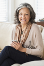 Hispanic woman using cell phone on sofa