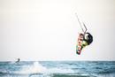 Man kiteboarding over ocean waves