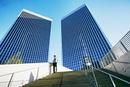 Black businessman standing under highrise buildings