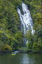 Caucasian friends paddling kayak under remote waterfall