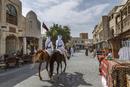 Men riding horses on Doha street, Doha, Qatar