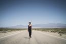 Caucasian woman walking on remote desert road