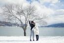 冬の湖畔でブランケットに包まるカップル
