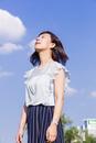 青空を背景に立つ女性