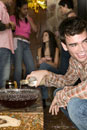 Man spiking bowl of punch at a party