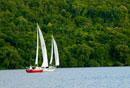 Two sailboats sailing along coastline