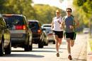 Couple jogging against street traffic