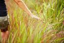 Woman walking through tall grass
