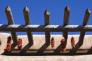 Chili Peppers Hanging From Beams of Adobe Building