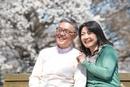 ベンチに座り桜を眺めるシニアカップル