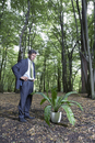 Business man watching potted plant in middle of forest