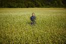花咲くソバ畑に立つ農夫