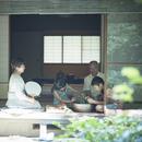 縁側でスイカや野菜を冷やす祖父母と孫たち