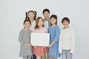 メッセージボードを持つ日本人と外国人の子供たち6人