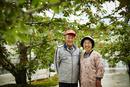 サクランボ畑に立つ笑顔の農家夫婦
