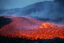 Boulder rolling in lava flow at dusk during eruption of Mount Etna volcano, Sicily, Italy.