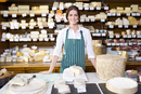 Saleswoman standing at counter with cheese in cheese shop