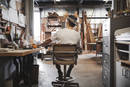 Rear view of carpenter sitting on chair at workshop