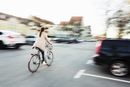 Rear view of businesswoman riding bicycle on city street