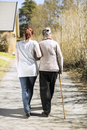 Rear view of senior woman and female home caregiver walking