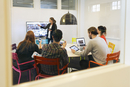 Businesswoman giving presentation during conference call in board room of creative office