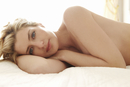 Portrait of nude woman laying on bed