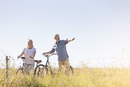 Senior couple bike riding in sunny rural field under blue sky