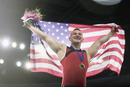 Enthusiastic male gymnast celebrating victory holding American flag on winners podium