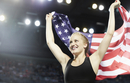 Smiling female runner running victory lap with American flag