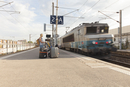 France, Nice, Woman with baby (6-11 months) on railroad station platform