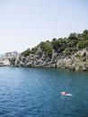 Turkey, Mugla, Marmaris, Man floating on mattress by rocky coast