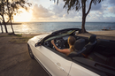 USA, Hawaii, Oahu, Banzai Pipeline, Mid adult woman watching sunset in convertible car at beach