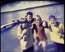 Four children, pre teenagers laughing on the lake shore. Summer vacation.