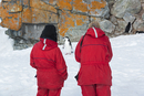 Two people looking at a Chinstrap Penguin on Halfmoon Island.