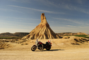 Motorcycle parked in front of a rock formation in a landscape.