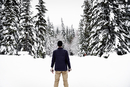 Rear view of a man standing in the snow in a forest in winter.