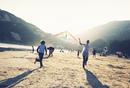 Children flying kites on a sandy beach.