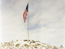 An American flag Stars and Stripes, flying from a flagpole on a small hillock.