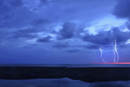 A lightning storm over the ocean. Forks of lightening emerging from clouds.