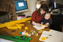 A woman seated with her baby on her lap writing in a notebook. Craft material and tools. Tabletop in a workroom.