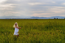 Blond girl in a white summer dress running through a field.
