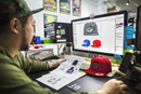 A man, a designer working on screen creating designs for baseball caps.