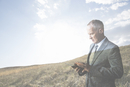 Digital composite businessman using digital tablet against hill