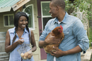 rural couple holding chicken and collected eggs