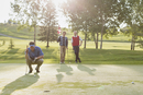 golfer focussed on putt while friends watch