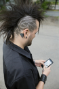 Cool man with shaved head and mohawk texting with cell phone