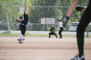 Middle school girl softball pitcher pitching to batter